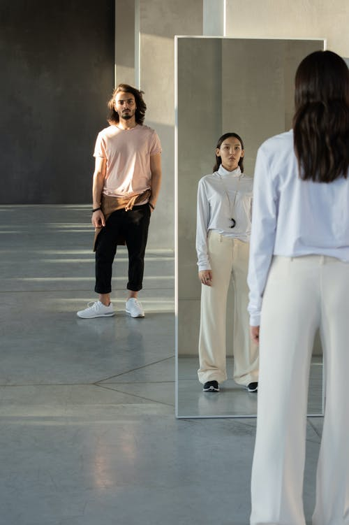Woman in White Bluish Long Sleeve Shirt and White Pants Standing In Front of a Mirror