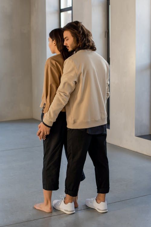 Woman and Man in Beige Sweatshirts and Black Pants Standing on Gray Floor Tiles