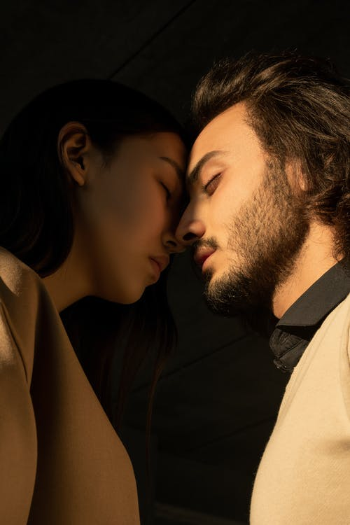 Close-up Photo of Couple with Their Eyes Closed Facing Each Other In Front of Dark Background