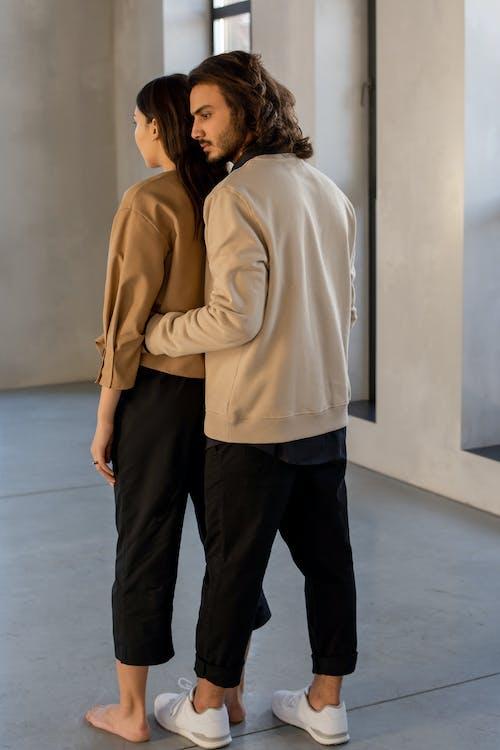 Wanita Dan Pria Dengan Kemeja Lengan Panjang Beige Dan Celana Hitam Berdiri Di Lantai Abu Abu