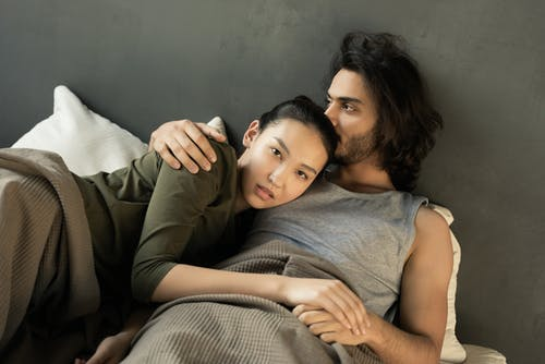 Woman in Green Top Lying on a Man's Chest in Bed
