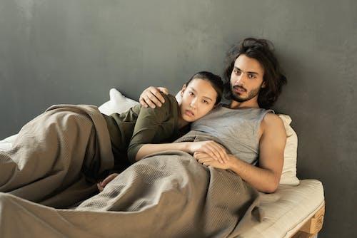 Wanita Dengan Tank Top Abu Abu Berbaring Di Samping Tempat Tidur Gadis Berkemeja Putih