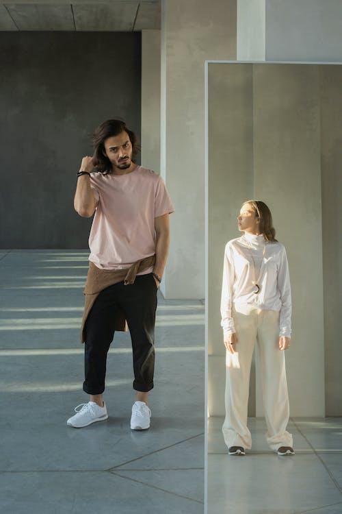 Pria Berkancing Merah Muda Dan Celana Hitam Berdiri Di Lantai Biru