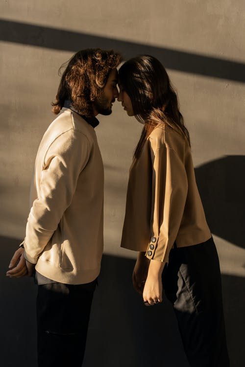 Man in Beige Sweatshirt Kissing Woman in Beige Blazer and Black pants