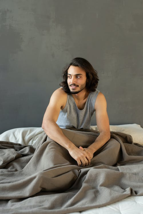 Man in Gray Tank Top Sitting on Bed