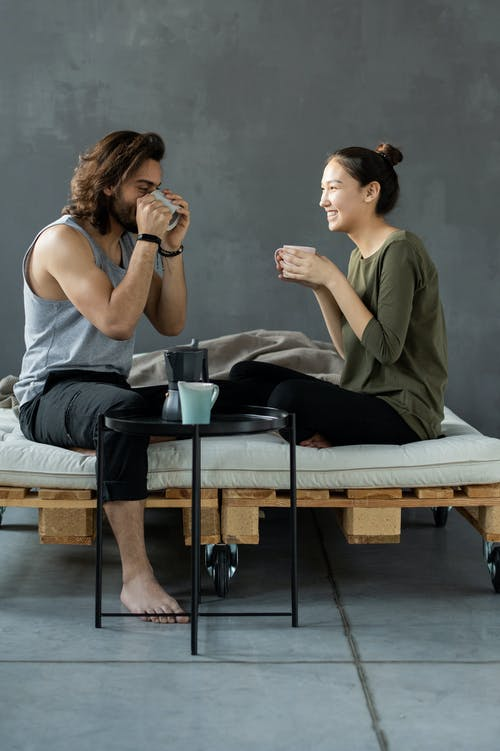 Man and Woman Sitting on a Bed Having Breakfast
