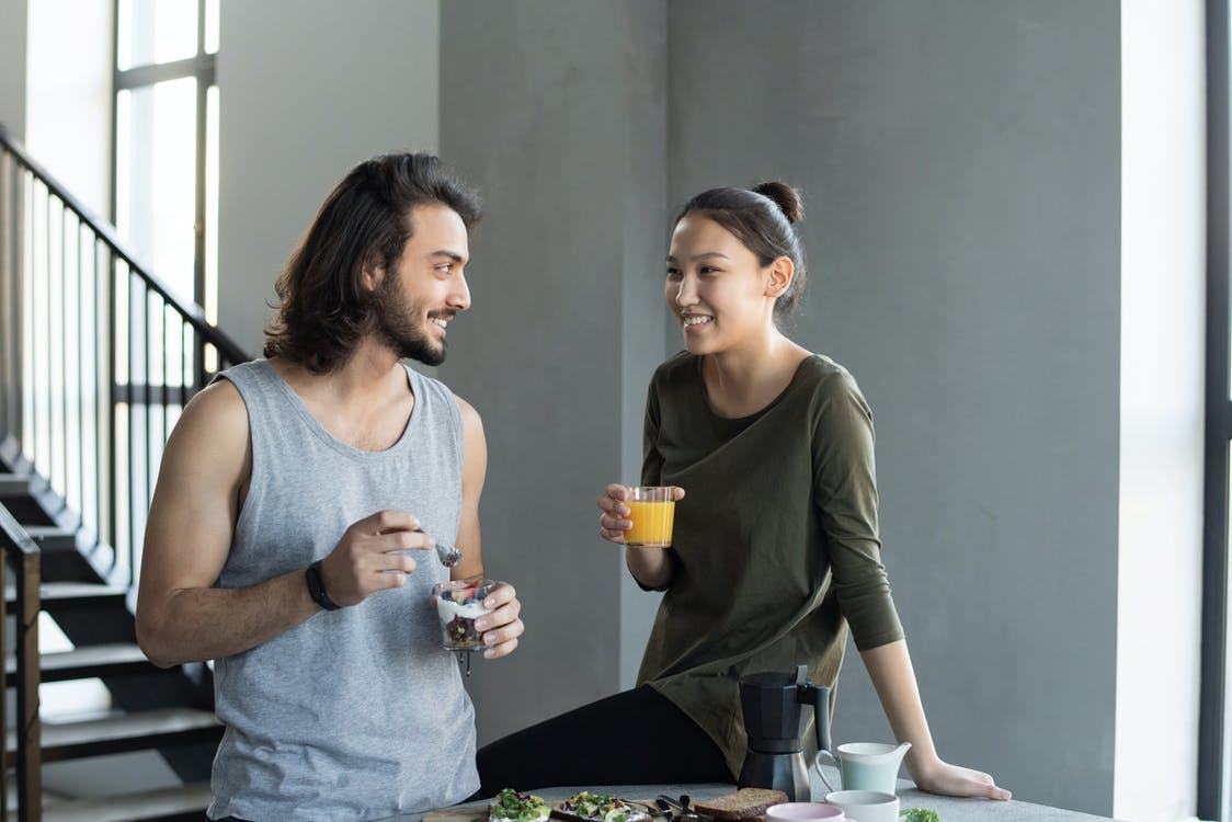 Man in Grey Tank Top and Woman in Green Top Holding Clear Drinking Glass