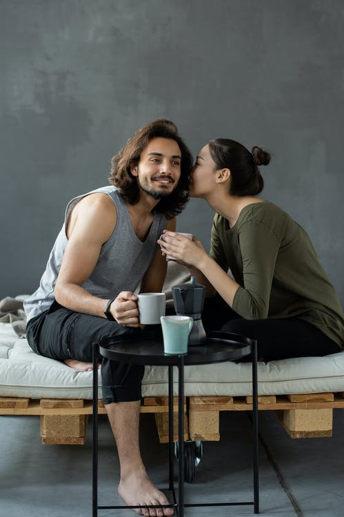 Woman in Green Top Whispering to a Man in a Gray Tank Top