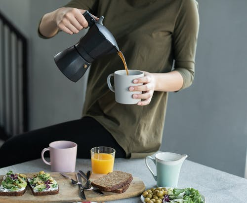 Woman in Green Top Pouring Coffee in a White Mug