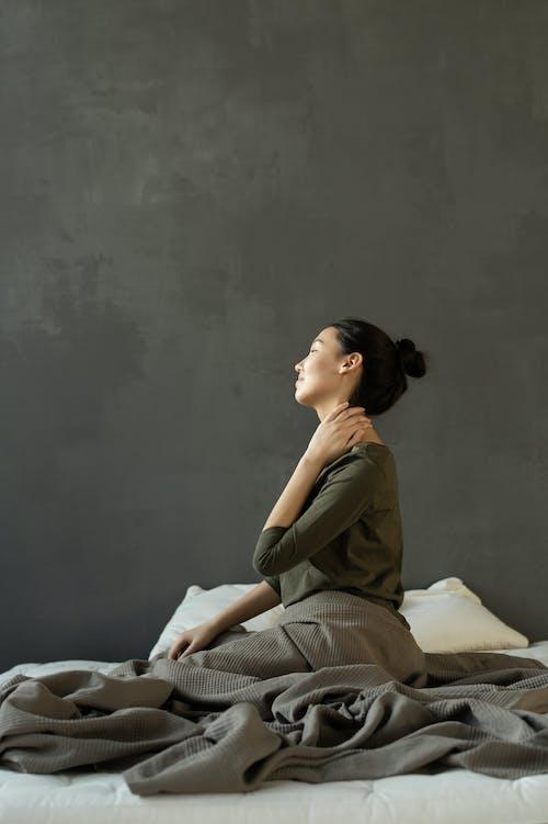 Wanita Dengan Gaun Abu Abu Duduk Di Tempat Tidur
