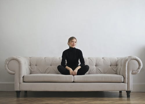 Photo of Woman in Black Long Sleeve Turtleneck Sitting on Grey Couch In Front of Gray wall