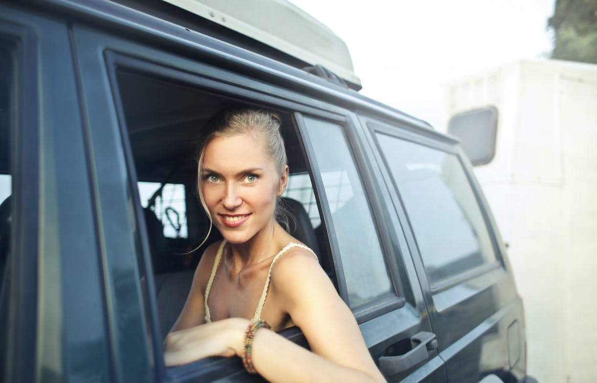 Content blonde sitting on backseat in car