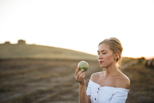 Selective Focus Photo of Woman in White Off Shoulder Top Holding Green Apple
