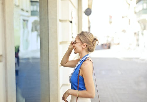 Selective Focus Side View Photo of Smiling Woman in Blue Top Standing on Sidewalk Looking Through Store Window