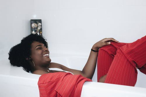 Photo of Laughing Woman in Red Pinstripe Suit Lying Inside Bathtub