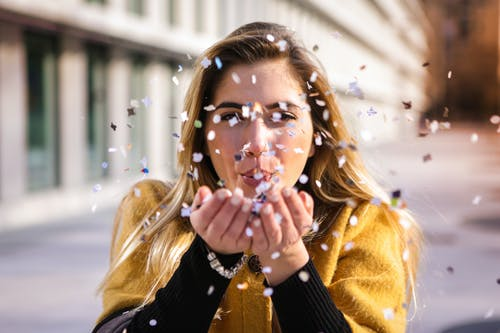 Selective Focus Photo of Woman in Black and Brown Coat Blowing Confetti From Her Hands