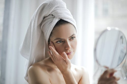 Young female with bare shoulders and towel on head holding small mirror and checking skin with it in bathroom