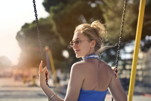 Selective Focus Photo of Smiling Woman in Blue Top and Sunglasses Sitting on Swing Looking Back