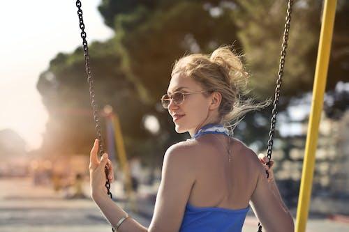 Foto Fokus Selektif Wanita Tersenyum Dengan Atasan Biru Dan Kacamata Hitam Duduk Di Ayunan Melihat Ke Belakang