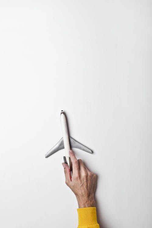 Male hand with white toy plane