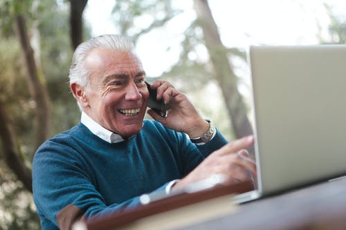 Selective Focus Photo of Smiling Elderly Man in Blue Sweater Sitting by the Table Talking on the Phone While Using a Laptop