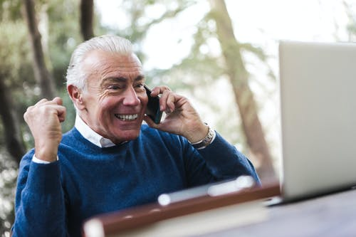 Selective Focus Photo of Excited Elderly Man in Blue Sweater Sitting by the Table Talking on the Phone While Using a Laptop