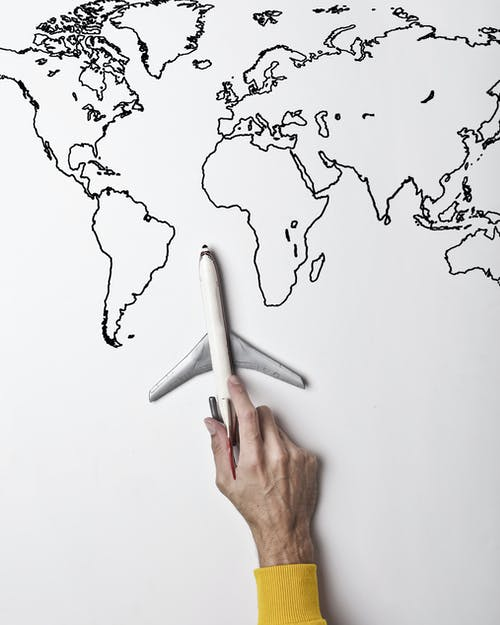 Person holding small toy airplane against black and white map as concept of travel and vacation