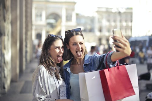 Cheerful young women with shopping bags taking selfie on street