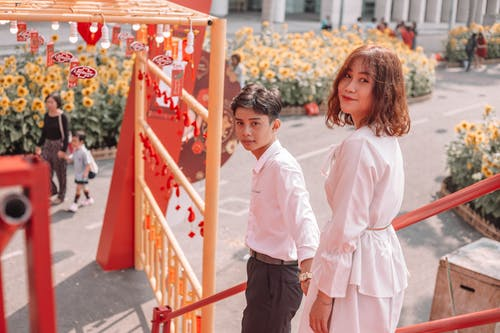 Ethnic siblings standing on stairs near road with blooming sunflowers