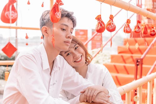 Young ethnic man in formal outfit standing near cheerful girlfriend leaned on beam under small colorful decorative bags near staircase in sunlight