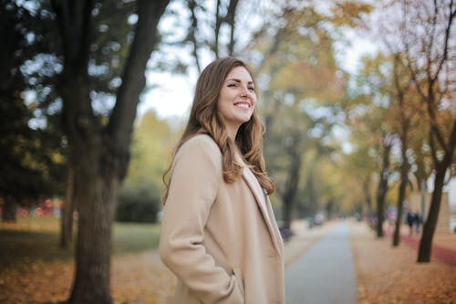 Selective Focus Photo of Smiling Woman in Brown Coat Standing on Road  Near Tree