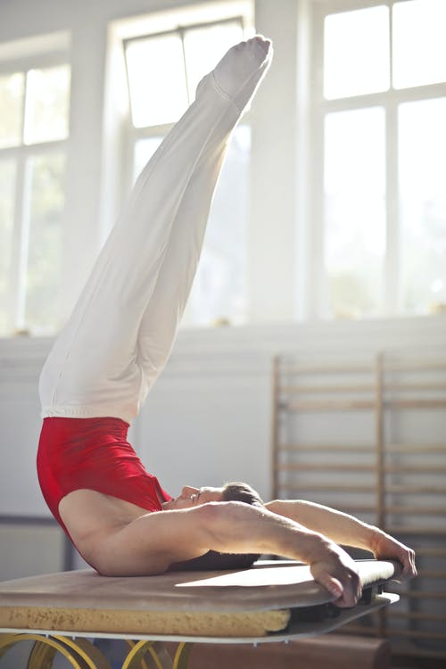 Flexible athlete performing shoulder stand in contemporary gym