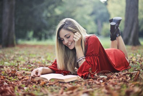 Smiling Woman in Red Dress Lying on Brown Dried Leaves on Ground Reading Book