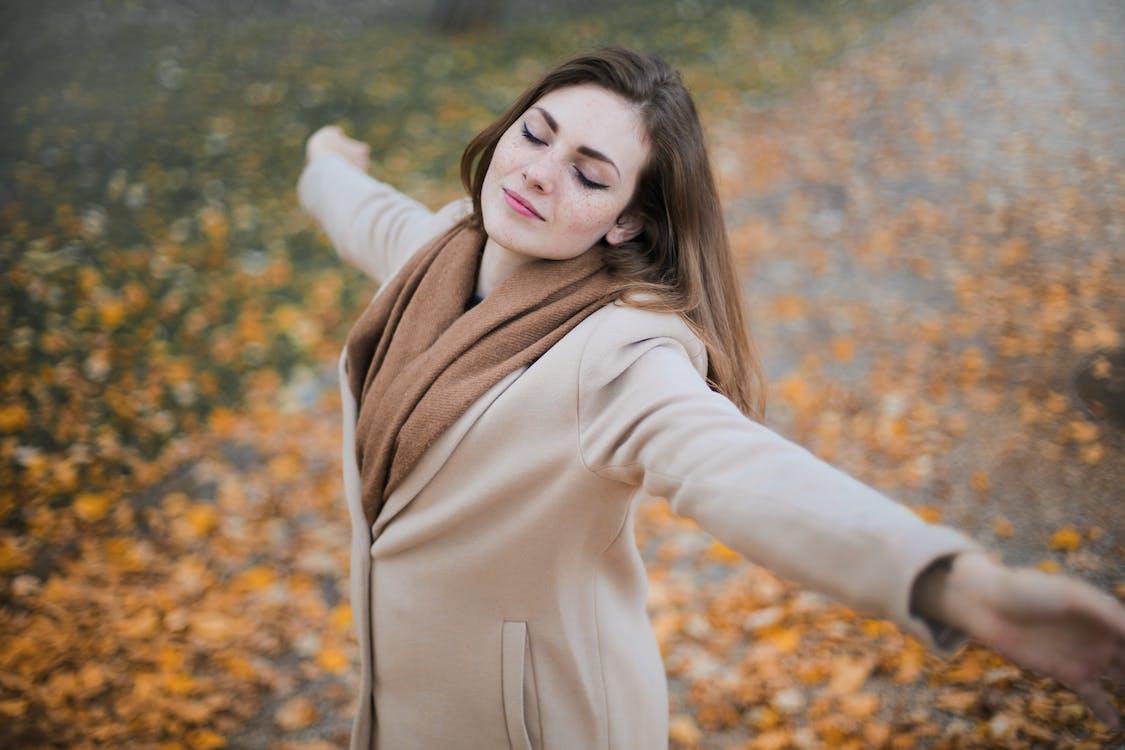 茶色の葉の上に立っているベージュの長袖コートの女性
