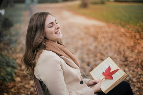 Selective Focus Photo of Laughing Woman in Brown Coat Holding a Book While Sitting in a Park Bench