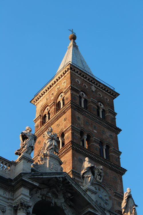 Old tower of famous catholic church decorated with sculptures