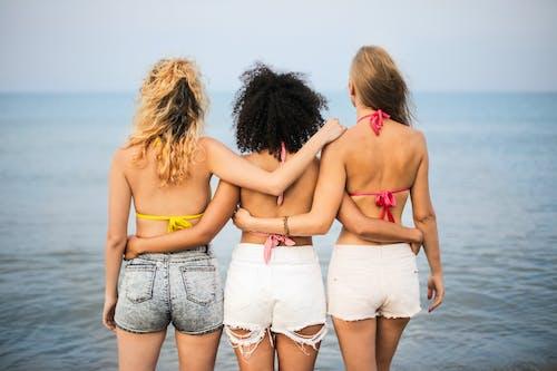 Selectieve Aandacht. Achteraanzicht Foto Van Drie Vrouwen In Bikinitopjes En Spijkerbroek Die Samen Staan Met Uitzicht Op De Oceaan