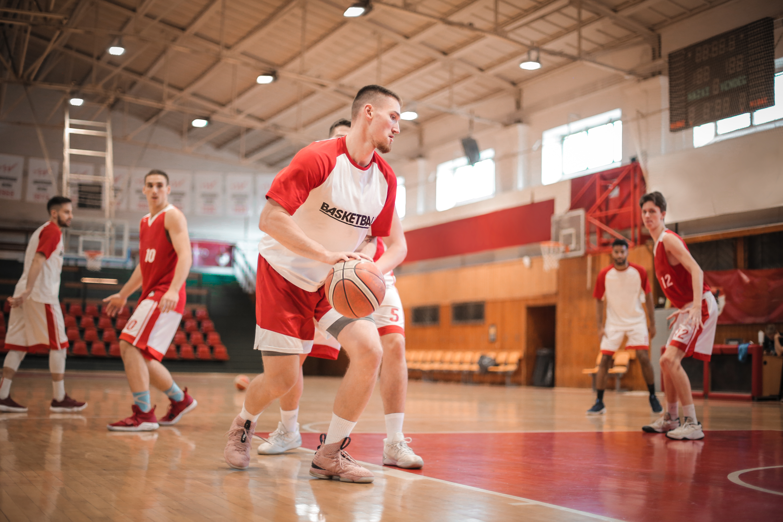 men playing basketball inside gym