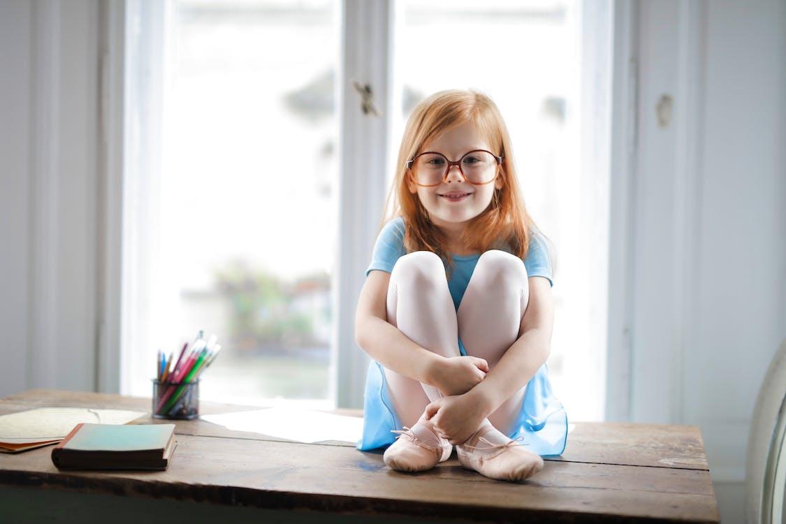 Gelukkig Schattig Klein Meisje In Glazen Zittend Op Tafel In Lichte Woonkamer