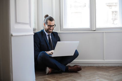 Man in Navy Blue Suit Jacket Sitting Down Using Macbook