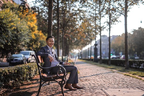 Man in Grey Suit Sitting on Park-bench Using Laptop