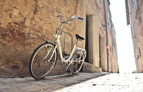 Bicycle parked on narrow street against old building with shabby walls in town