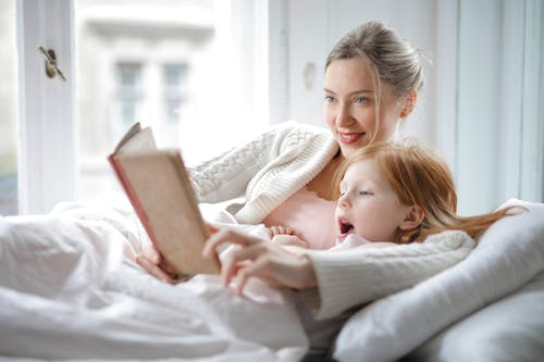 Cheerful young woman hugging cute little girl and reading book together while lying in soft bed in light bedroom at home in daytime