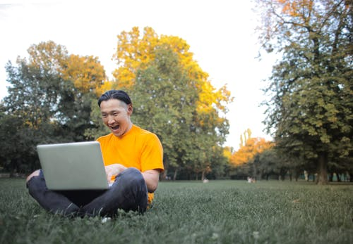 Man in Yellow Crew Neck T-shirt and Gray Pants Sitting on Green Grass Field Using Laptop