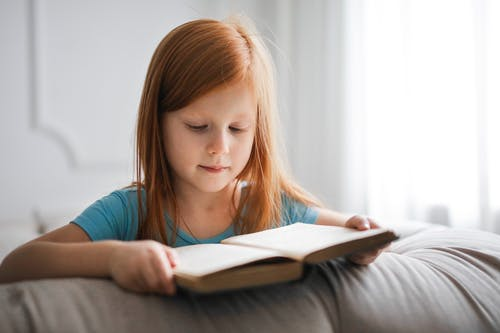 Girl in Blue T-shirt Reading Book