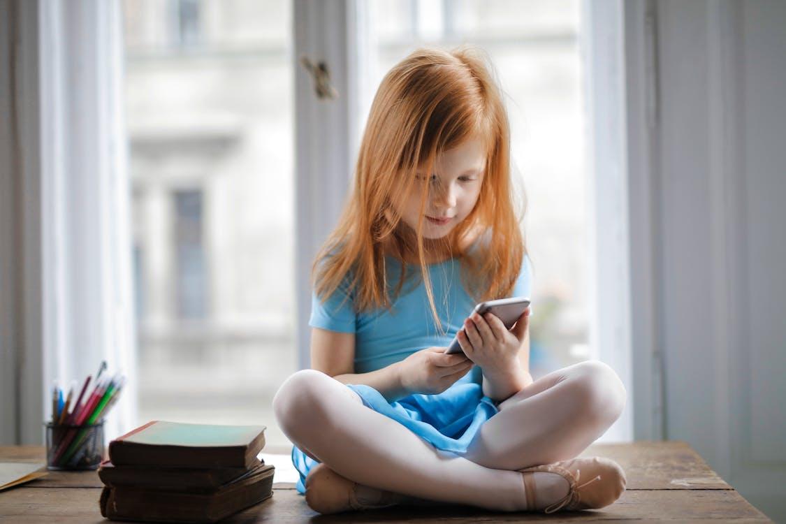 Ruhiges Kleines Ingwermädchen, Das Auf Tisch Sitzt Und Smartphone Im Hellen Wohnzimmer Benutzt