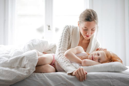 Mother caressing daughter while resting together in bed at home