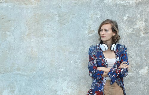 Photo of Woman in Blue and White Floral Long Sleeve Shirt With Headphones on Her Neck Leaning on Gray Wall Looking Away