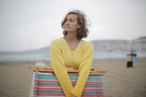 Calm female tourist with folded deckchair standing alone on seashore in overcast weather