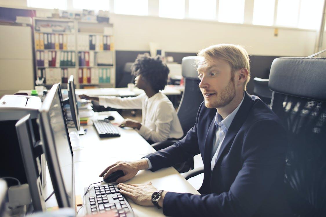 オープンスペースのオフィスで民族の同僚の横にあるコンピューターを使用して大人の驚いたエグゼクティブ男性